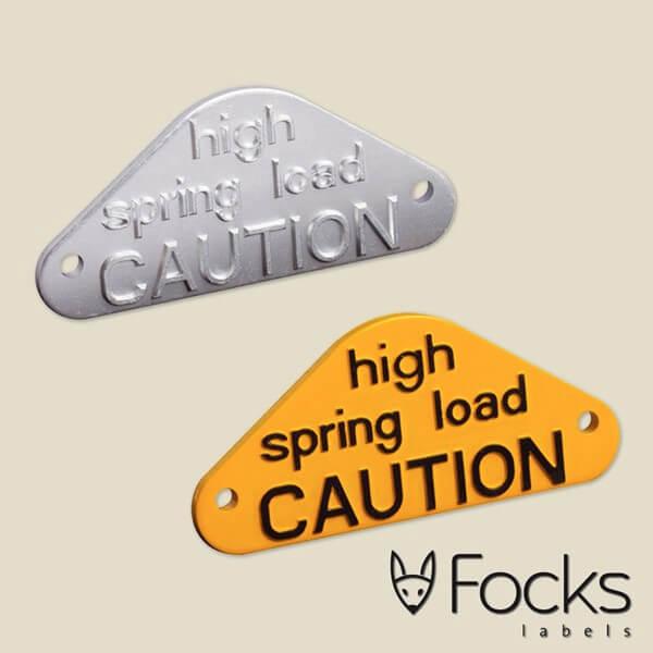 Waarschuwingssymbool van gegoten aluminium, in 2 kleuren gespoten, tekst 1,5 mm dik opliggend, met 2 boorgaten voor montage.