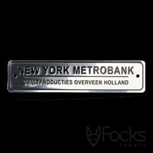 Naamlabel voor parkbanken, glanzend aluminium gepreegd. De gepreegde delen zijn zwart bedrukt. Met boorgaten.